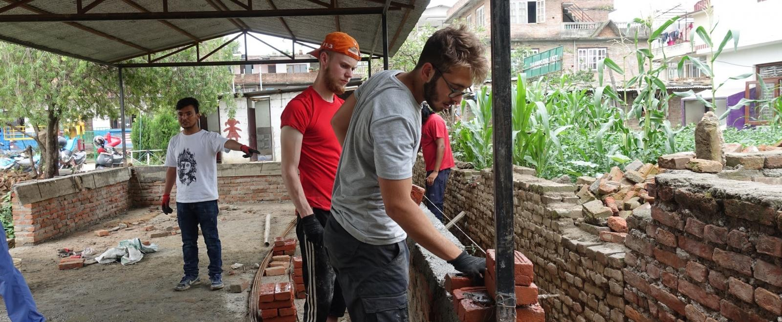 Building volunteers lay bricks for classroom walls in Nepal